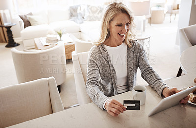 Buy stock photo Shot of a mature woman using a credit card and digital tablet while relaxing at home
