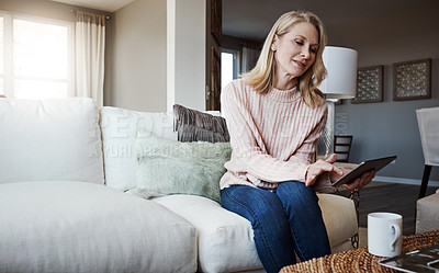 Buy stock photo Shot of a mature woman using a digital tablet while relaxing on the sofa at home