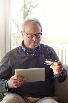 Buy stock photo Cropped shot of a senior man using a tablet and credit card at home