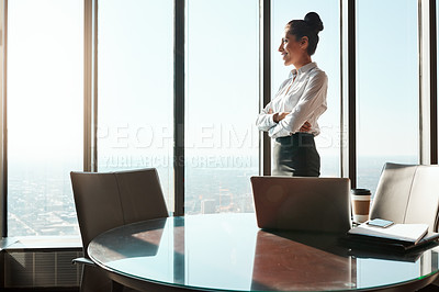 Buy stock photo Shot of a young businesswoman looking out the window in an office