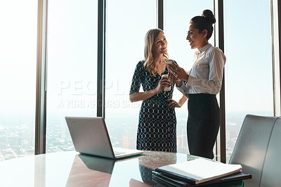 Buy stock photo Shot of a businesswoman showing her colleague something on her cellphone in an office