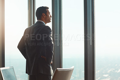 Buy stock photo Rearview shot of a handsome young businessman standing with his hands on his hips in the office