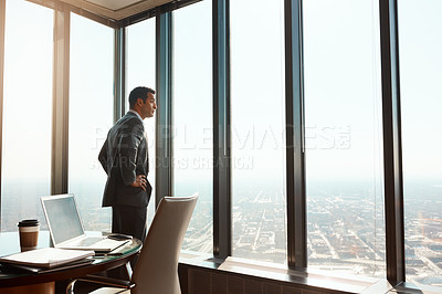 Buy stock photo Cropped shot of a handsome young businessman standing with his hands on his hips in the office