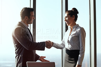 Buy stock photo Cropped shot of two young businesspeople shaking hands in their office