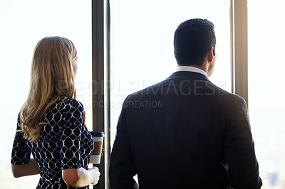Buy stock photo Rearview shot of two young businesspeople standing in their office