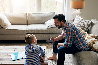 Buy stock photo Shot of a father helping his little son with his homework