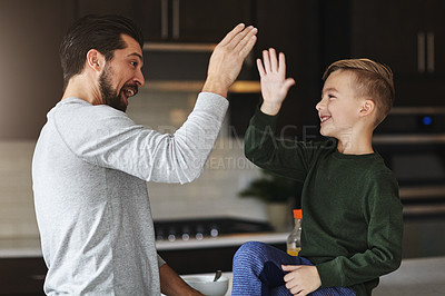 Buy stock photo Cropped shot of a handsome young man and his son high fiving in the kitchen