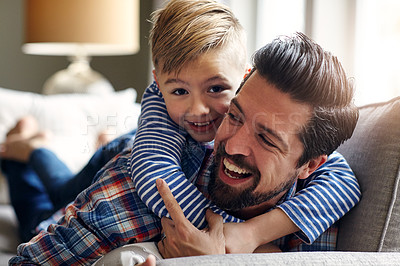 Buy stock photo Shot of a father and his little son bonding together at home