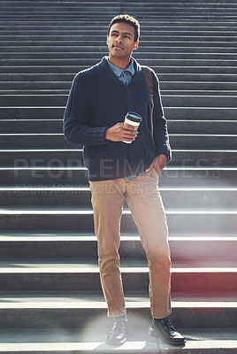 Buy stock photo Shot of a handsome young businessman walking through the city