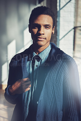 Buy stock photo Shot of a handsome young businessman standing in a modern office