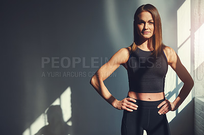 Buy stock photo Cropped portrait of an attractive young sportswoman standing with her hands on her hips