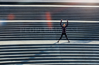 Buy stock photo High angle shot of an attractive young sportswoman doing jumping jacks on outside stairs