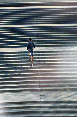 Buy stock photo High angle shot of a handsome young sportsman running up and down stairs outside