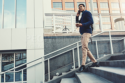 Buy stock photo Shot of a young businessman using a mobile phone while walking through the city