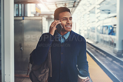 Buy stock photo Shot of a young businessman using a mobile phone while walking through the subway