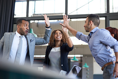 Buy stock photo Cropped shot of a group of young businesspeople high fiving while standing in the boardroom