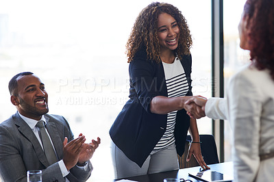 Buy stock photo Cropped shot of two young businesswomen shaking hands during a meeting in the boardroom