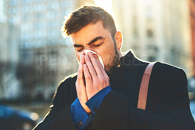 Buy stock photo Shot of a irritated looking young man blowing his nose with a tissue while walking the busy streets of the city in the morning