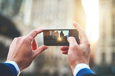 Buy stock photo Shot of an unrecognizable man taking a picture of the sun rising over buildings in the city during the morning hours
