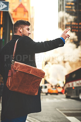 Buy stock photo Shot of a cheerful young man listening to music while he tries to signal a taxi to get to work in the busy streets of the city