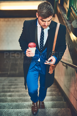 Buy stock photo Shot of a focused young businessman texting on his phone and drinking coffee while walking up a flight of stairs in a subway during the morning hours