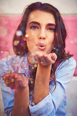 Buy stock photo Portrait of a beautiful young woman blowing confetti outside