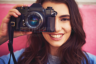 Buy stock photo Portrait of a beautiful young woman holding a dslr camera and posing against a wall outside