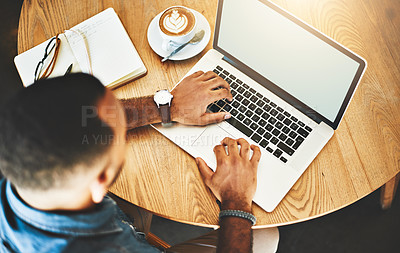 Buy stock photo High angle shot of a young man working on a laptop in a cafe
