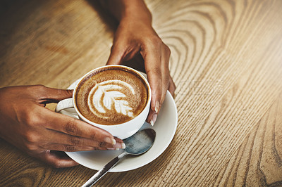 Buy stock photo High angle shot of an unrecognizable woman holding a cup of coffee decorated with froth art