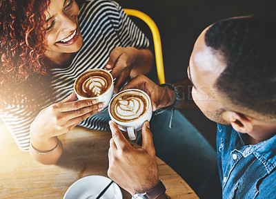 Buy stock photo High angle shot of an affectionate young couple sitting in a coffee shop