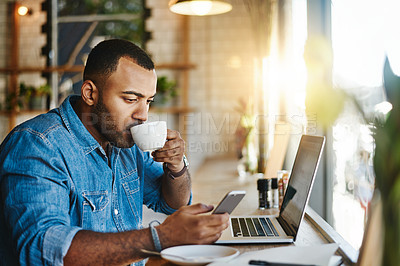 Buy stock photo Shot of a handsome young man drinking coffee while working working in a cafe