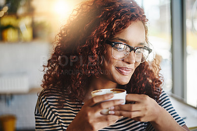 Buy stock photo Shot of an attractive young woman enjoying a cup of coffee in a cafe