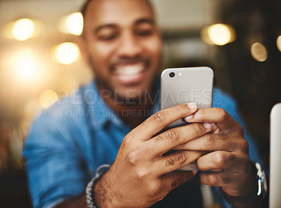 Buy stock photo Closeup shot of a young man using a cellphone in a cafe
