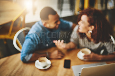 Buy stock photo High angle shot of a young couple working on a laptop while sitting in a coffee shop