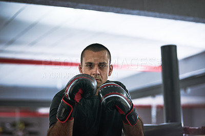 Buy stock photo Cropped portrait of a young male athlete training inside a boxing ring