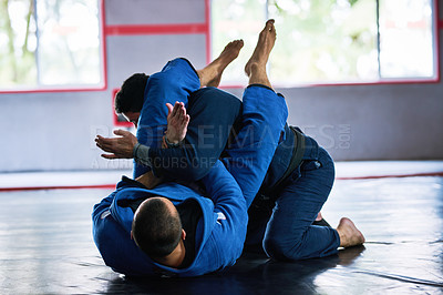 Buy stock photo Full length shot of two young male athletes sparring on the floor of their dojo