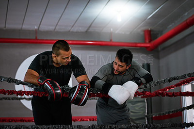 Buy stock photo Cropped shot of two young male athletes standing in a boxing ring after a sparring session