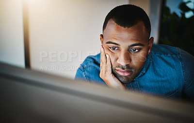 Buy stock photo Shot of a young businessman looking bored while working during a late night in a modern office