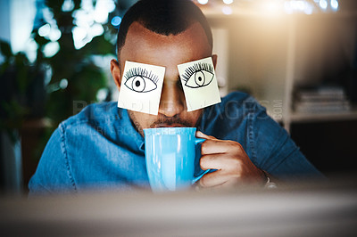 Buy stock photo Shot of a young businessman working late at work with sticky notes covering his eyes and drinking coffee