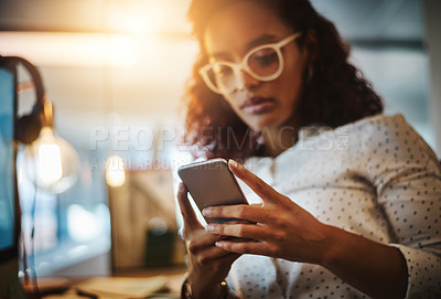 Buy stock photo Cropped shot of a young businesswoman using a mobile phone during a late night at work