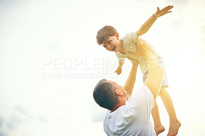 Buy stock photo Cropped shot of a father tossing his adorable son into the air outside