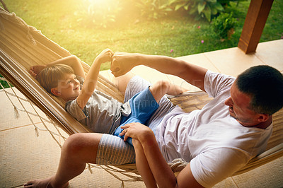 Buy stock photo Cropped shot of a father and his adorable son chilling on the hammock outside