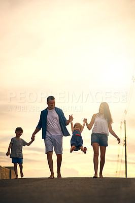 Buy stock photo Shot of a young family taking a walk down the road outside
