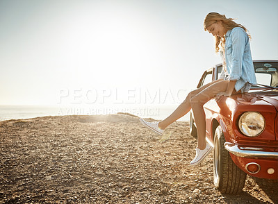 Buy stock photo Shot of a beautiful young woman relaxing on the hood of her car on a road trip
