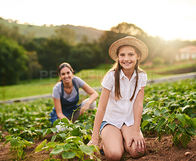 Buy stock photo Portrait of a young girl working on the family farm with her mother in the background