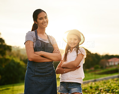 Buy stock photo Cropped portrait of an attractive young woman and her daughter standing with their arms folded on the family farm
