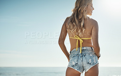 Buy stock photo Rearview shot of an attractive young woman enjoying her day on the beach