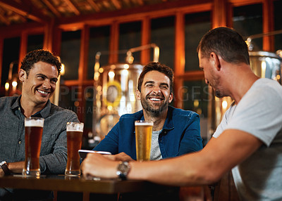 Buy stock photo Shot of a group of young friends seated at a table together while enjoying a beer inside a bar