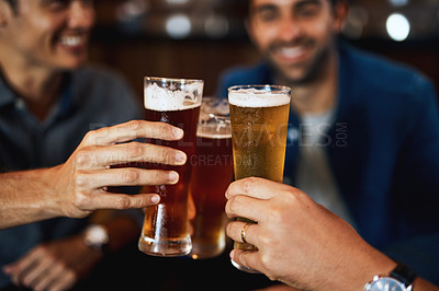 Buy stock photo Closeup of a group of young friends seated at a table together while enjoying a beer and celebrating with a celebratory toast inside a bar