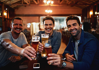 Buy stock photo Portrait of a group of young friends seated at a table together while enjoying a beer and celebrating with a celebratory toast inside a bar